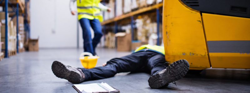 An accident in a warehouse. Woman running towards her colleague lying on the floor next to a forklift.